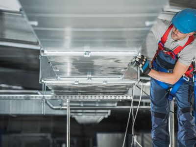 Industrial Theme. Warehouse Heating and Cooling System Installation by Professional Caucasian Technician. Commercial Building Ventilation Rectangle Canals. Air Distribution.